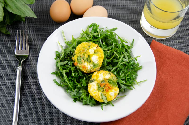 Muffin-pan-frittatas on bed of arugula on plate