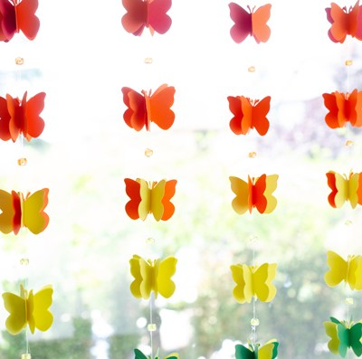 Butterfly garland hung in window, close up