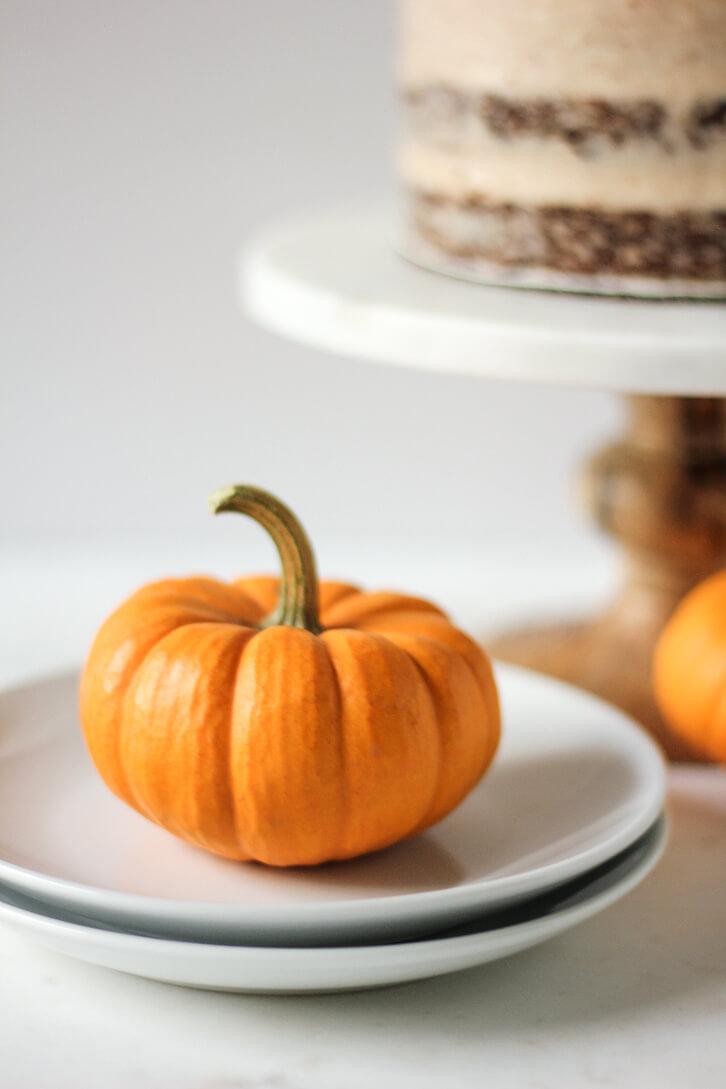 A mini pumpkin as festive decor for this six layer pumpkin carrot cake