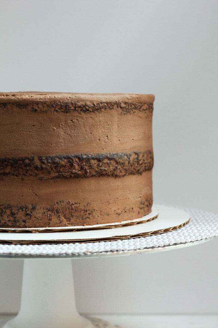 A three layer chocolate cake with a crumb coat of chocolate buttercream
