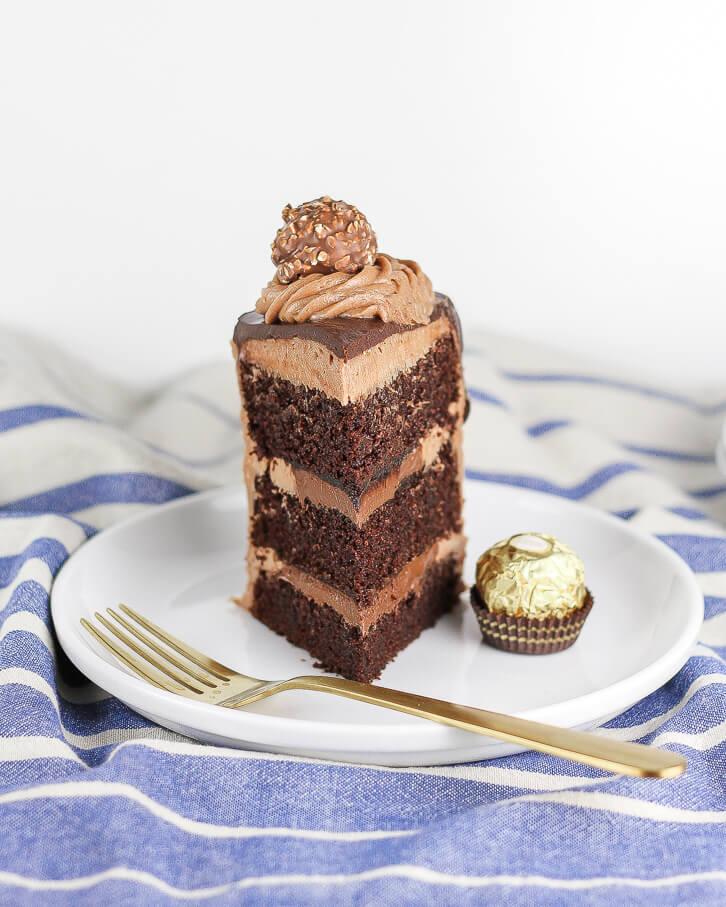 A slice of Nutella chocolate cake with a chocolate hazelnut truffle