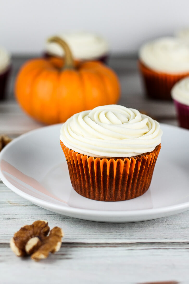 A pumpkin carrot cupcake with a swirl of cream cheese frosting