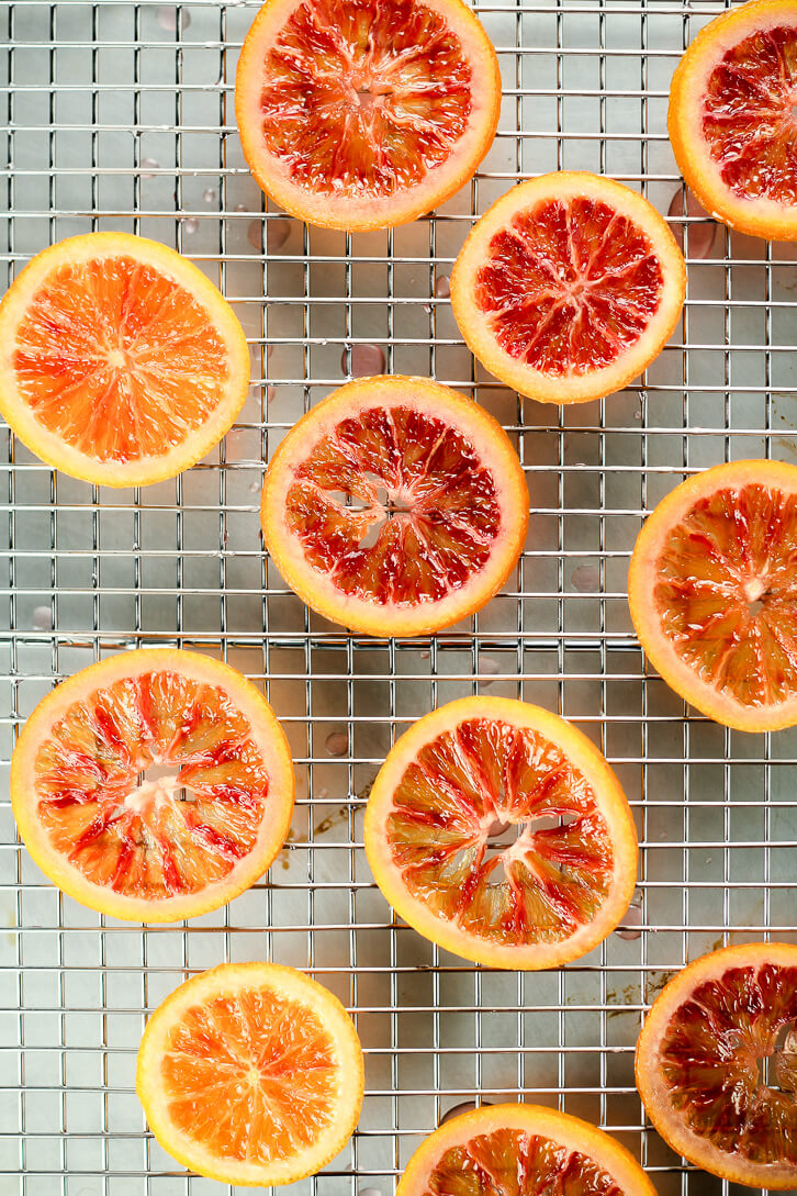 Candied blood orange slices drying on a wire rack