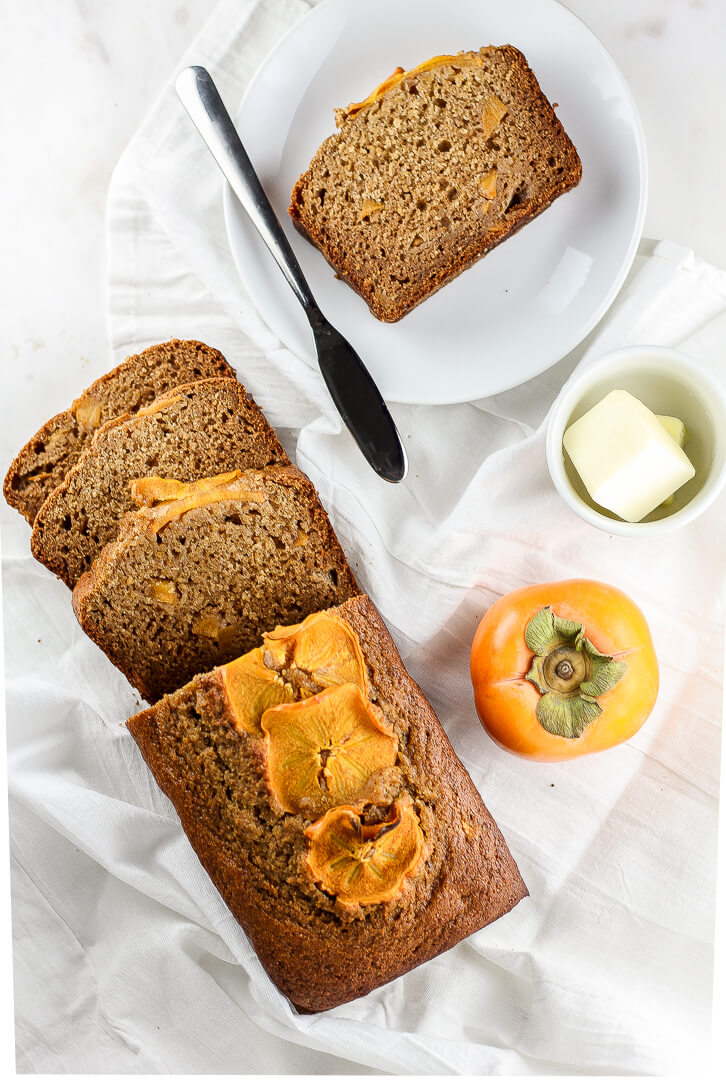 A sliced loaf of persimmon bread served with butter - Persimmon Bread - Flour Covered Apron