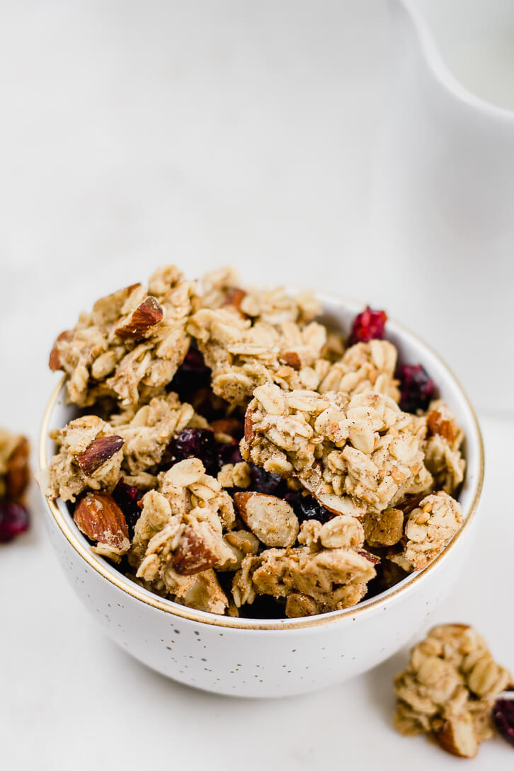 A close-up view of large granola clusters filled with cranberries and almonds.
