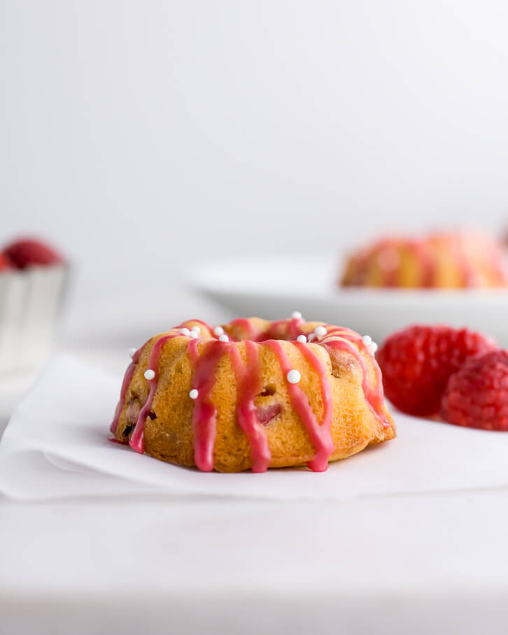 A punch raspberry glaze and white sugar pearls make these raspberry rhubarb mini bundt cakes celebration-ready!