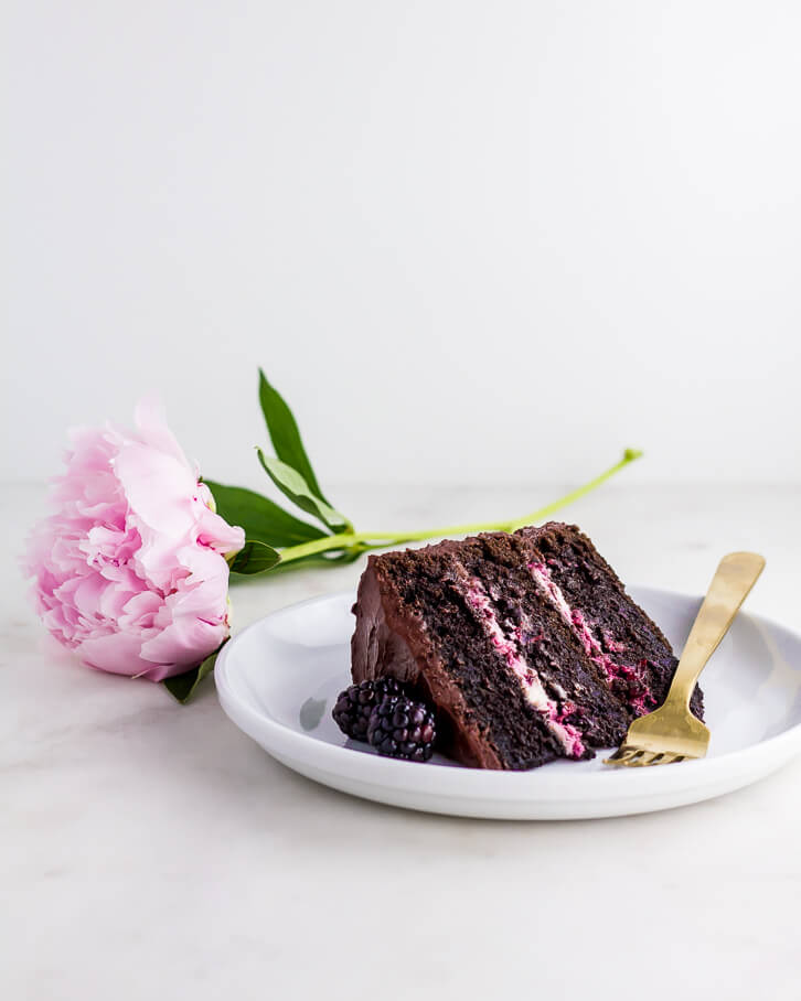 A slice of blackberry chocolate cake with blackberry mascarpone filling and blackberry chocolate frosting | Flour Covered apron