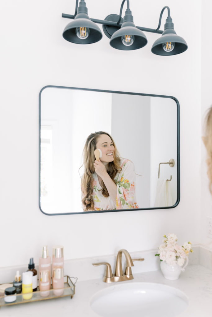 Caroline using a facial dry brushing technique in the mirror.
