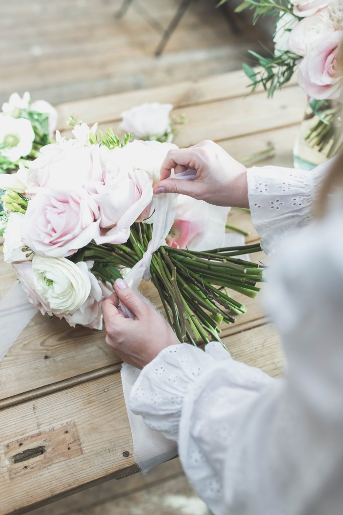 Zoe florist at Flourish and Grace Bristol creates a wedding bridal bouquet and ties with ribbon