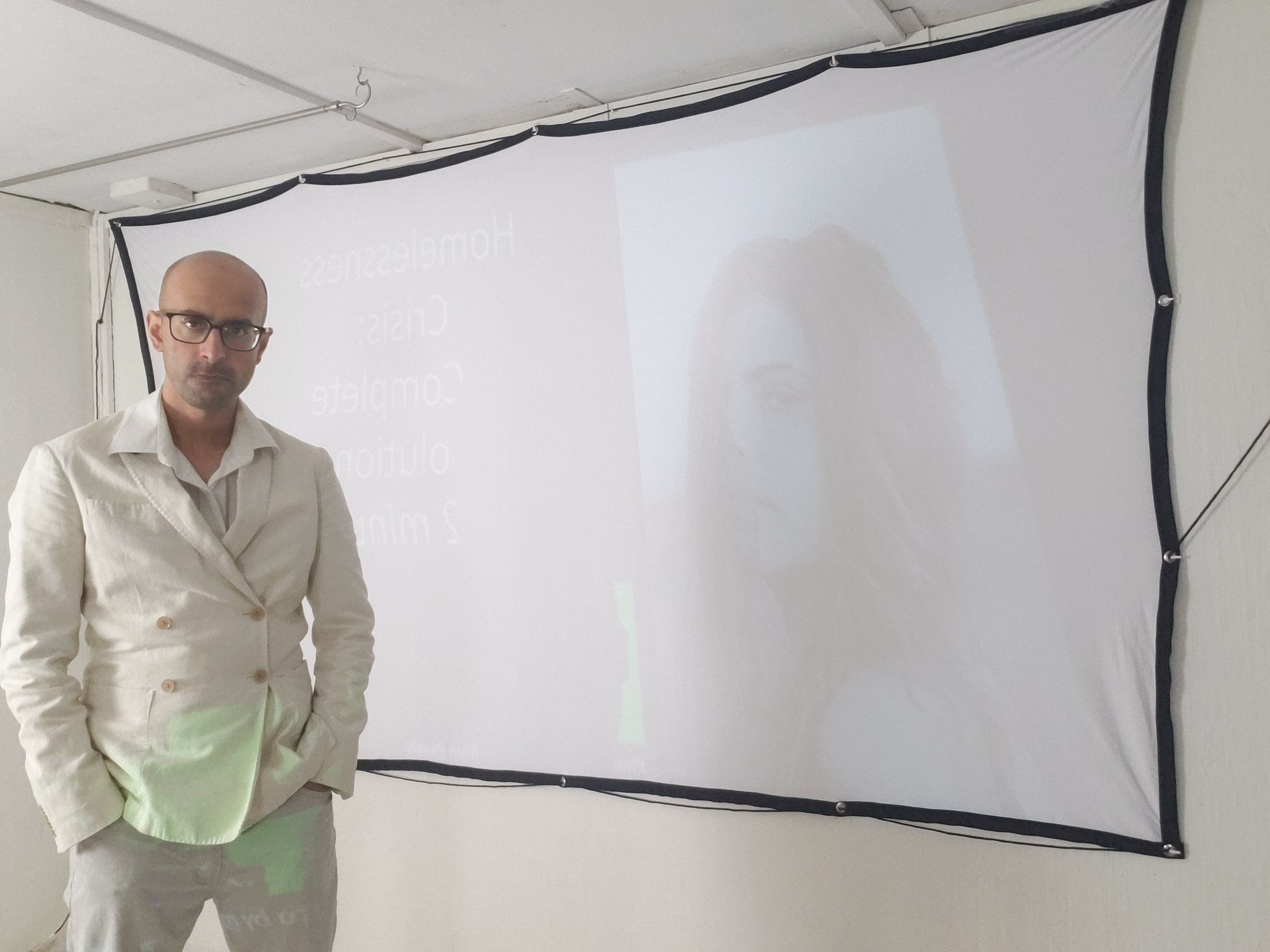 Salman Shuaib standing infront of a projected image