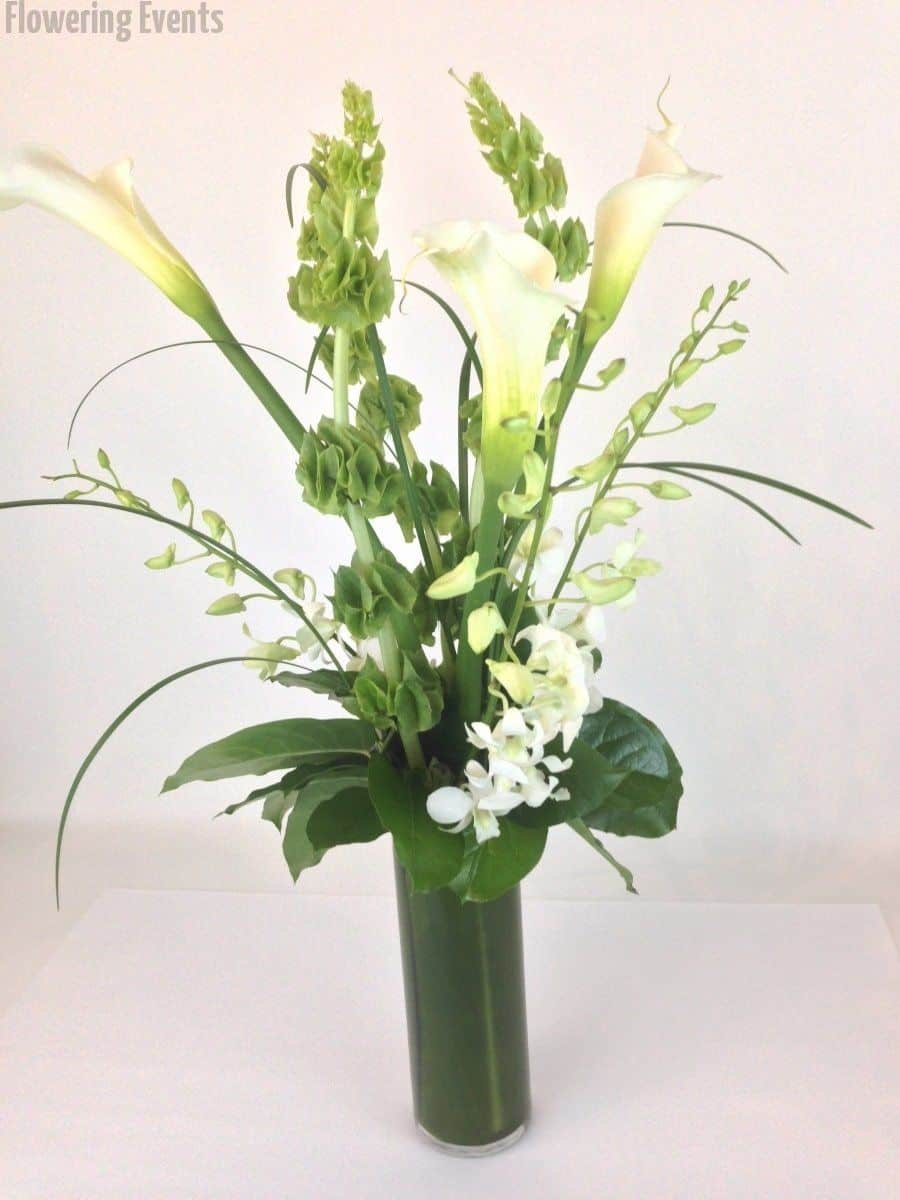 Vase arrangement of white and green, callas, bells of Ireland, and orchids.