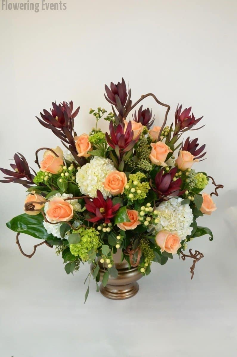 Urn arrangement of roses, hydrangea, leucodendron, and hypericum