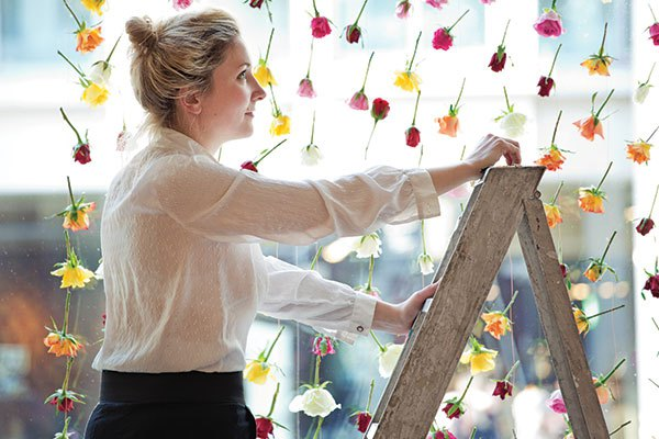 Artist Rebecca Louise Law completes a floral wall in the window of her London gallery. Photo courtesy of Rebecca Louise Law