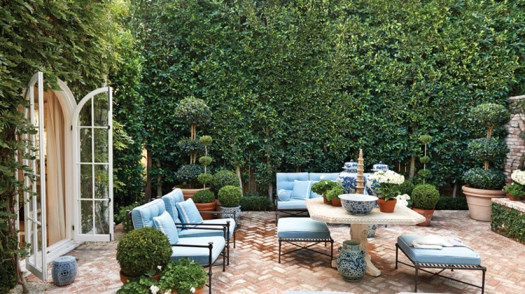 At Sikes' own home, a terrace becomes a natural extension of indoor spaces with its blue-and-white furnishings and accessories, and ficus-covered walls.