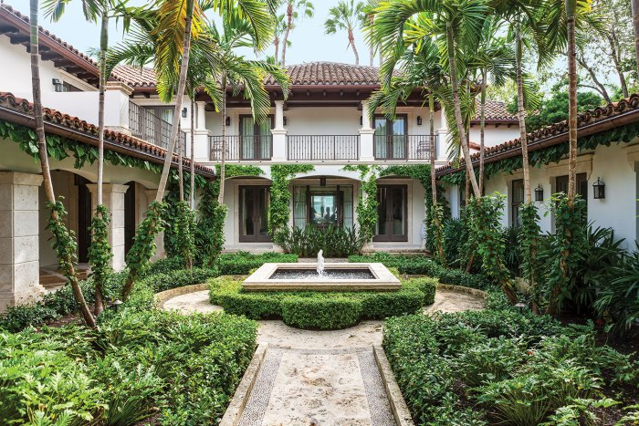 Photo of a courtyard garden designed by Fernando Wong. It is surrounded on three sides by a two-story white stucco structure with a tile roof. A covered patio with columns wraps around the left and back side. The garden features ferns, palm trees and climbing greener. The limestone path leads to a circular patio with a square fountain at the center, which is surrounded by a low cotoneaster hedge.