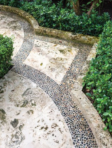 Photo of limestone patio designed by Fernando Wong with a pebble inlay border.