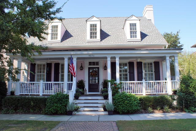 Pale pink cottage with white porch railings and dormer windows on the second floor, located on Bay Street in Norfolk, Virginia