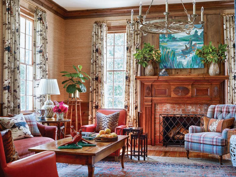 Photo of the Martin family's study created by interior designer James Farmer. Red leather chairs, a plaid armchair and a painting featuring blues and greens bring color to the room, which features a neutral grass wallcovering, natural heart pine paneling and a brick fireplace with antique natural-wood wood mantel. A threadbare Oriental rug ties the room together.