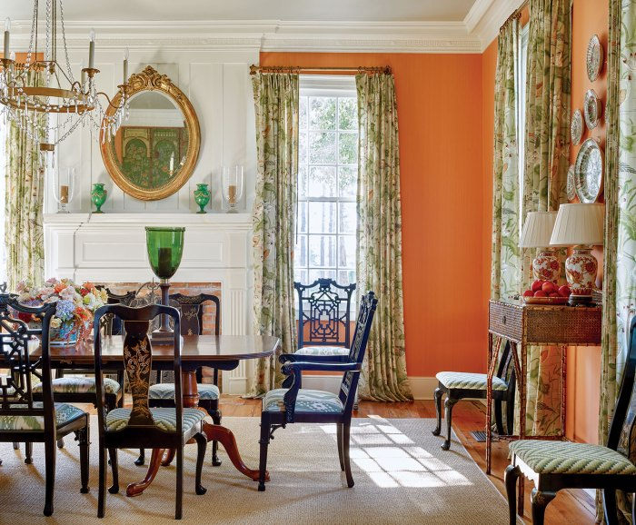 Photo of the dining room designed by James Farmer at McCurdy Plantation, featuring apricot walls, botanical-patterned curtains, a white-painted fireplace mantel and crown molding and a neutral area rug.