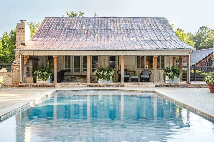 A large blue pool leads the covered brick porch the pool house, which features a weathered metal roof