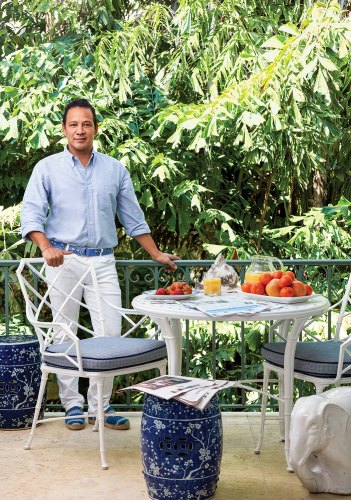 Photo of a Fernando Wong wearing white pants, a light blue shirt, and a deep blue belt and shoes. He is standing at a set of white wrought iron table and chairs.