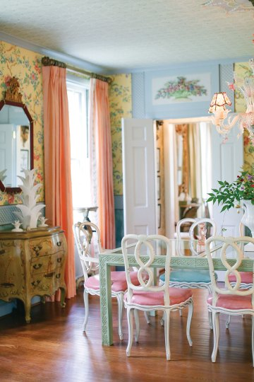 John Loecke and Jason Oliver Nixon's dining room features yellow wallpaper bearing a botanical print, a glass-top table with a carved wooden base painted light green, white painted chairs with pink upholstered seats, and peach floor-to-ceiling curtain panels