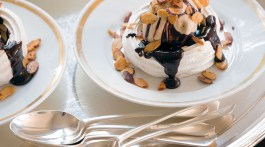 A tray of plated meringues topped with ice cream, chocolate sauce, and nuts, with silver spoons to the side, a recipe by Julia Reed