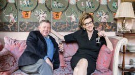 """Julia Reed and interior designer and writer Patrick Dunne sit beneath a Directoire """"papier peint"""" screen in the dining room of his town home in the Faubourg Marigny."""