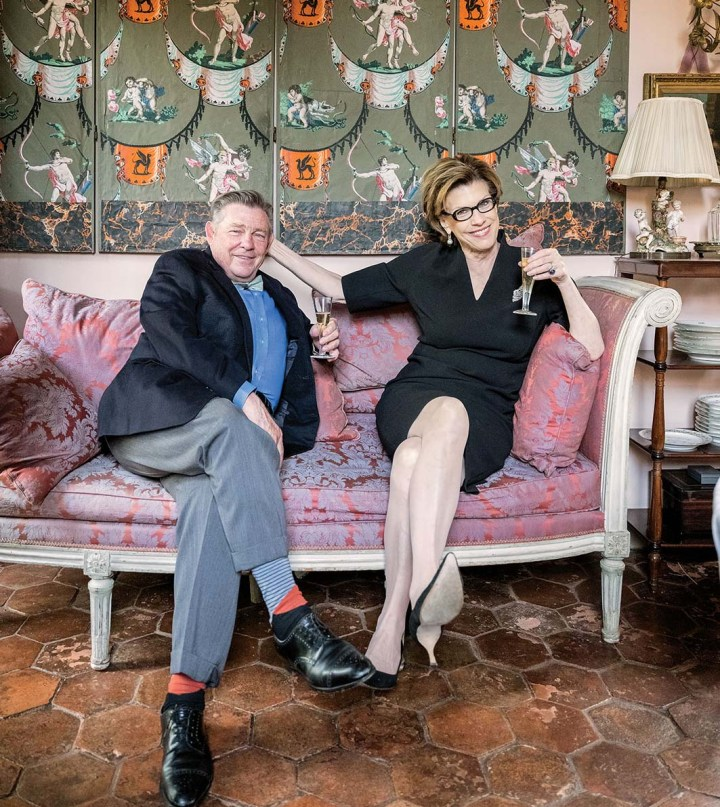 Julia Reed and Patrick Dunne sit cross-legged and sipping champagne on a pink-upholstered, wood-frame sofa in Dunne's New Orleans home