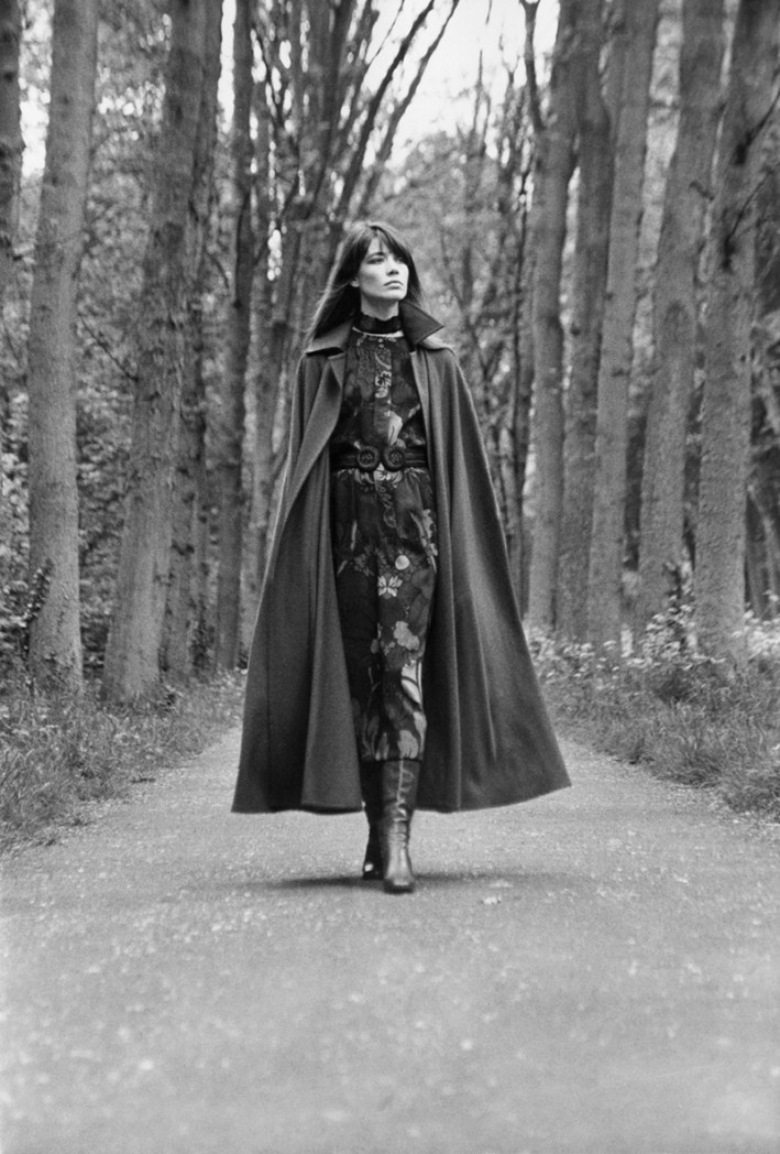 Black-and-white photo of Françoise Hardy walking down a tree-lined path