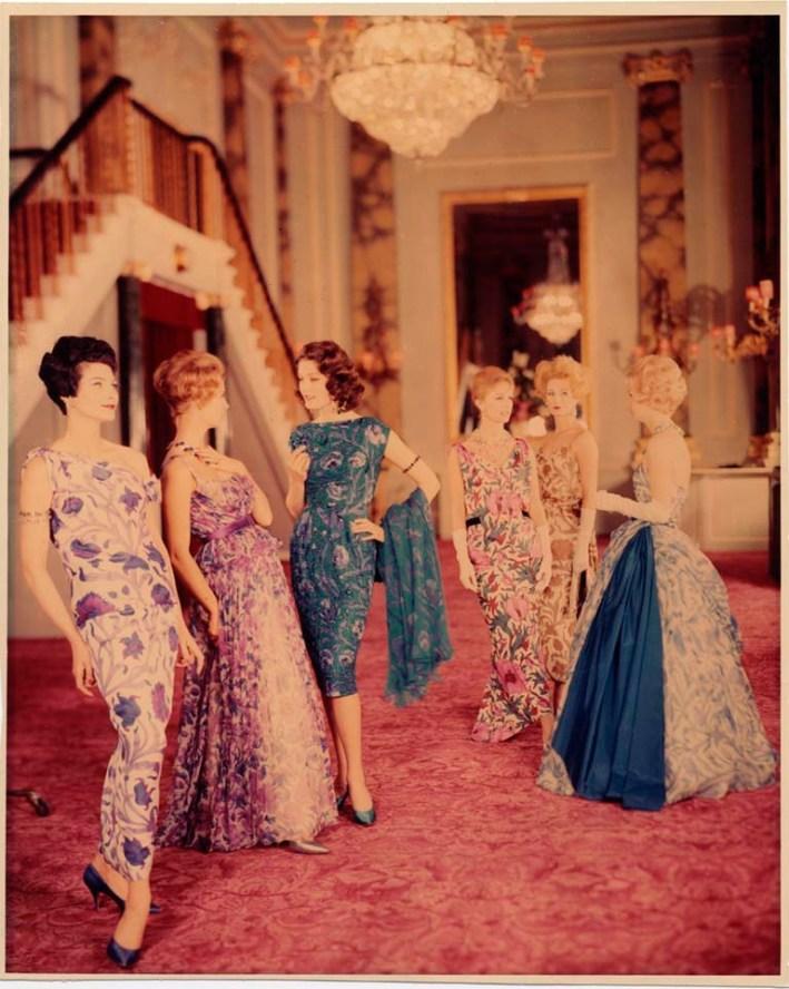 Six women model botanical-print gowns in an opulent setting