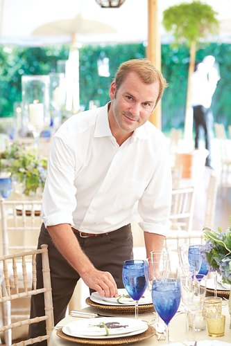 Reed McIlvaine in white button-up and black pants standing behind a table set for a party