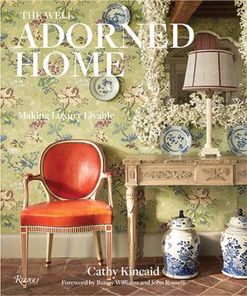 Book cover for The Well Adorned Home by Cathy Kincaid (Rizzoli New York, 2019), $50, featuring a bright orange delicate antique chair, a soothing green botanical wallpaper, entry table and mirror, and blue-and-white porcelain.