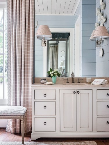 "Crystal sconces are hard-wired into a wide, frameless mirror to optimize natural light in the master bathroom. Light blue paint distinguishes the shiplap walls of the master bath from the other rooms, while white and neutral gingham curtain panels and a soft white sink vanity with a light neutral stone countertop maintain consistency with the materials Francie Hargrove used throughout her ""chic mountain house"" design theme."