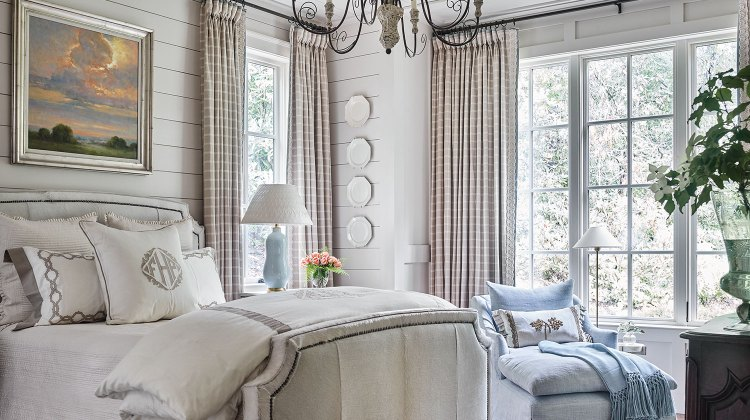 A blue chaise with matching throw and a glazed lamp add a pop of light blue, while a landscape painting featuring a morning sky also breaks up the neutral palette.