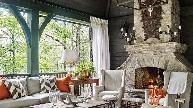 Other mountain house decor ideas from this screen porch include a sofa and chairs in a light upholstery. Throw pillows and an afghan bring in a punch of bright orange that complements the muted teal millwork. A large white-and-neutral striped area rug and a pair of chevron-print throw pillows add visual interest through pattern. And though upholstered in a light fabric, a curved upholstered bench with deep, plush tufting makes a bold statement. An antique, simple wood desk holds a chunky glass lamp and a large copper pot holding a green plant. A large modern coffee table with a wood top and streamlined metal base, along with wood variety of stools and small side tables, complete the space.