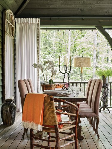 The screen porch features wood tones and other earthy hues, with a rough-hewn wooden table for 8. Francie Hargrove's choices for mountain house decor on the porch include moth orchids in a copper pot, faux bois candlesticks and plant stand with fern, a large pottery jug with a dark glaze, an orange afghan with white fringe, a white curtain panel, and 6 leather upholstered dining chairs with grommets that compliment that pair of Appalachian hoop chairs at earth end of the table.