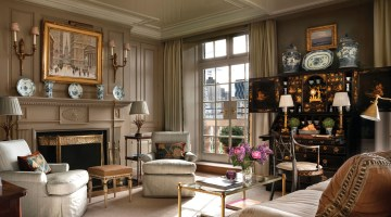 A fireplace surround with classic woodwork embellishments is pained the same neutral color as the wall panels and curtain panels. Touches of blue-and-white, gold, and bronze, along with a colorful vase of pink and purple blooms, punctuate the serene space with color. A mullioned window offers a view of the city.