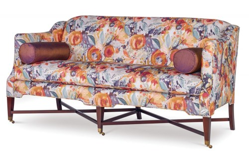 "Delicate sofa upholstered in a botanical pattern of blue and ""chrysanthemum orange"" flowers"