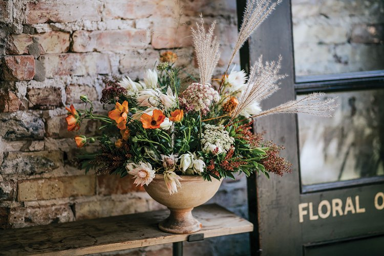 A Kelly Marie Thompson floral design in a low compote vase