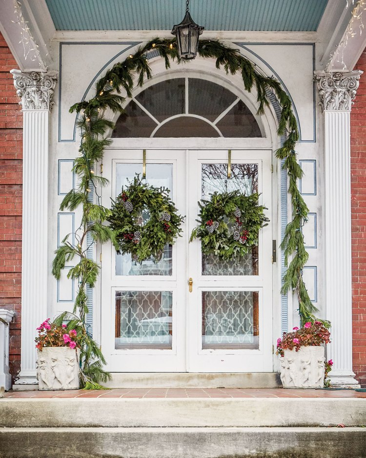 The front entry of a historic home on Monument Avenue, in Richmond, Virginia, features a holiday garland over the arched doorway, and a wreath on each side of the double door.