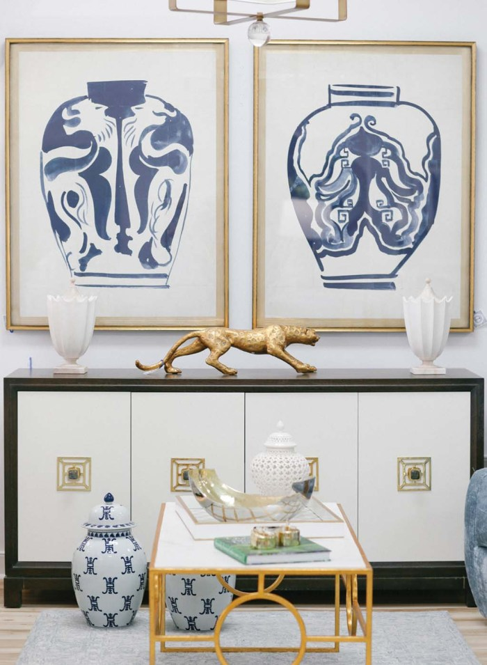 A shop scene from Beckon Home in Richmond, Virginia, including abstract art prints of large blue-and-white ginger jars, a modern console and a modern coffee with a gold metal vase, and other decorative accessories.