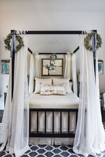 The wreaths are attached to the two front posts, with a third is attached to the canopy frame, centered above the headboard. Four airy white panels hang from each corner of the canopy