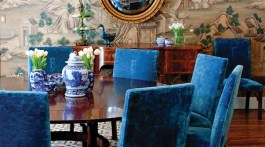 Dining room featuring deep blue velvet chairs around a circular table, a geometric print rug, a convex gold-framed circular mirror above the side board, and Gracie's 'Ming Village' wall covering