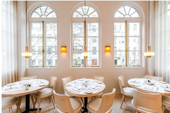 The light and air interior of JoJo, with white-on-white interior design and tall ample windows