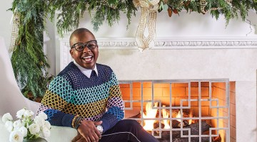 Atlanta floral designer Canaan Marshall, wearing a stylish crochet sweater, tailored dark pants a thin light strip along the outer seam, and loafers. The mantel is elaborately decorated with greenery and gold ribbon for the holidays.