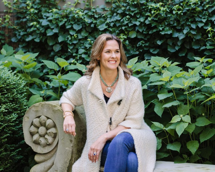 Jewelry designer Clara Williams, wearing a long neutral-colored cardigan sweater and jeans, sits on an elegant concrete bench against a lush green background