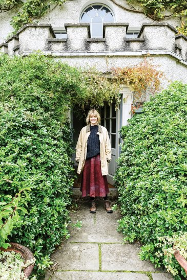 Glin Castle heiress Catherine FitzGerald, with chin-length wavy blond hair and a pleasant smile, wears rugged boots, a light tan farm jacket, a dark cable-knit sweater; and a full, ankle-length, burgundy skirt in a paisley print