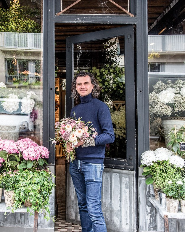 Parisian florist Eric Chauvin, wearing in worn jeans and navy turtleneck, stands at the open door of his French flower shop, holding a bouquet. On either side, window boxes are planted with pink and white flowering hydrangeas and trailing ivy.