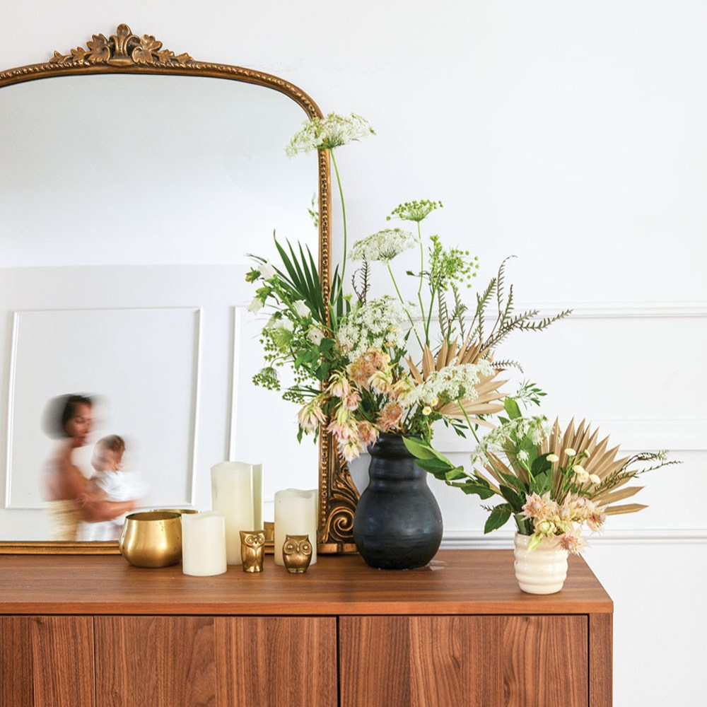 Two floral arrangements (one in a small white modern vase and the other in a larger, dark modern vase) sit to the right side on top of a mirror-topped wooden dresser. The mirror's reflection shows a blurred image of Monica Delgado walking by holding her young child